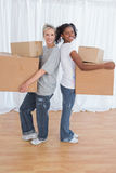 Smiling friends standing back to back holding moving boxes Royalty Free Stock Photography