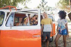 Smiling friends standing by camper van at campsite Royalty Free Stock Image