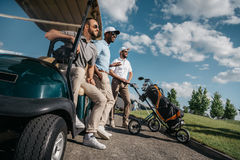 Smiling friends standing near golf cart and looking away. Group of smiling friends standing near golf cart and looking away Stock Image