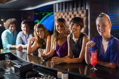 Smiling friends standing together at bar counter Royalty Free Stock Image