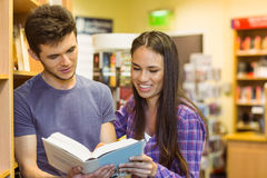Smiling friends student reading textbook Stock Image