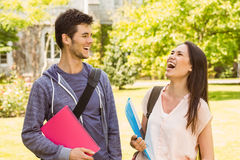 Smiling friends student standing with shoulder bag holding book Stock Photo
