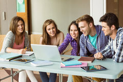 Smiling friends students using laptop Royalty Free Stock Photography