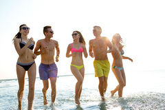 Smiling friends in sunglasses running on beach Royalty Free Stock Images
