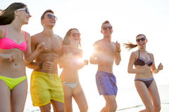 Smiling friends in sunglasses running on beach Royalty Free Stock Photos