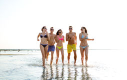 Smiling friends in sunglasses running on beach Stock Photos