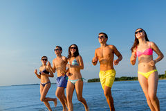 Smiling friends in sunglasses running on beach Royalty Free Stock Image