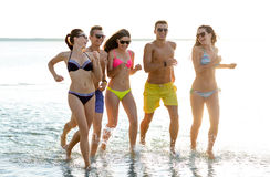 Smiling friends in sunglasses running on beach Stock Photography