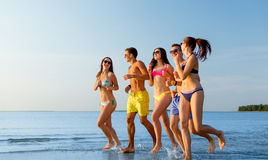 Smiling friends in sunglasses running on beach Royalty Free Stock Photo