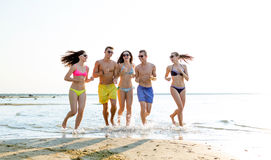 Smiling friends in sunglasses running on beach Stock Image