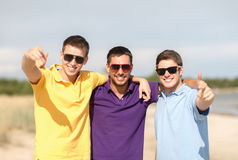 Smiling friends in sunglasses showing thumbs up. Friendship, summer vacation, holidays and people concept - group of smiling male friends in sunglasses showing Stock Image