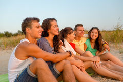 Smiling friends in sunglasses on summer beach. Friendship, happiness, summer vacation, holidays and people concept - group of smiling friends sitting beach stock images