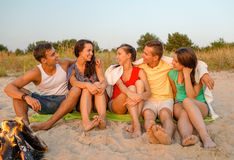 Smiling friends in sunglasses on summer beach. Friendship, happiness, summer vacation, holidays and people concept - group of smiling friends sitting near fire Stock Photo