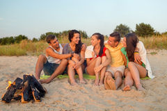 Smiling friends in sunglasses on summer beach. Friendship, happiness, summer vacation, holidays and people concept - group of smiling friends sitting near fire Stock Photos