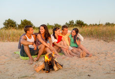 Smiling friends in sunglasses on summer beach. Friendship, happiness, summer vacation, holidays and people concept - group of smiling friends sitting near fire Stock Image