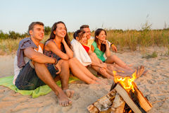 Smiling friends in sunglasses on summer beach. Friendship, happiness, summer vacation, holidays and people concept - group of smiling friends sitting near fire Royalty Free Stock Photos