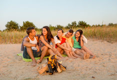 Smiling friends in sunglasses on summer beach. Friendship, happiness, summer vacation, holidays and people concept - group of smiling friends sitting near fire Stock Images