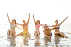 Smiling friends in sunglasses on summer beach. Friendship, sea, holidays, gesture and people concept - group of smiling friends wearing swimwear and sunglasses Stock Image