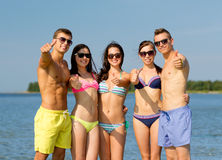 Smiling friends in sunglasses on summer beach. Friendship, sea, holidays, gesture and people concept - group of smiling friends wearing swimwear and sunglasses royalty free stock photos