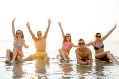 Smiling friends in sunglasses on summer beach. Friendship, sea, holidays, gesture and people concept - group of smiling friends wearing swimwear and sunglasses Royalty Free Stock Image