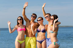 Smiling friends in sunglasses on summer beach. Friendship, sea, holidays, gesture and people concept - group of smiling friends wearing swimwear and sunglasses stock photos