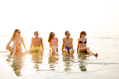 Smiling friends in sunglasses on summer beach. Friendship, sea, summer vacation, holidays and people concept - group of smiling friends wearing swimwear and Stock Photos