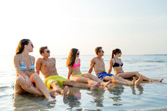 Smiling friends in sunglasses on summer beach. Friendship, sea, summer vacation, holidays and people concept - group of smiling friends wearing swimwear and Stock Photo