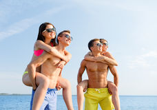 Smiling friends in sunglasses on summer beach Royalty Free Stock Image