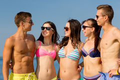 Smiling friends in sunglasses on summer beach Stock Photos