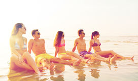 Smiling friends in sunglasses on summer beach. Friendship, sea, summer vacation, holidays and people concept - group of smiling friends wearing swimwear and Royalty Free Stock Photography