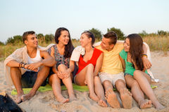 Smiling friends in sunglasses on summer beach. Friendship, summer vacation, holidays, gesture and people concept - group of smiling friends sitting on beach Royalty Free Stock Photo