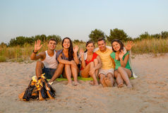 Smiling friends in sunglasses on summer beach. Friendship, summer vacation, holidays, gesture and people concept - group of smiling friends sitting near fire and Stock Photo