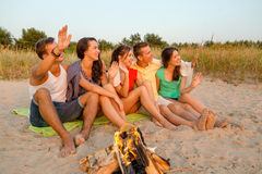 Smiling friends in sunglasses on summer beach. Friendship, summer vacation, holidays, gesture and people concept - group of smiling friends sitting near fire and royalty free stock images