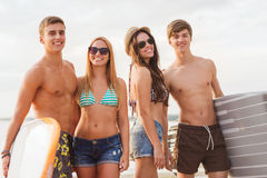 Smiling friends in sunglasses with surfs on beach Stock Photo