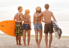 Smiling friends in sunglasses with surfs on beach Royalty Free Stock Photography