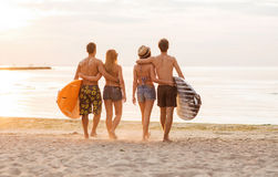 Smiling friends in sunglasses with surfs on beach. Friendship, sea, summer vacation, water sport and people concept - group of smiling friends wearing swimwear royalty free stock images