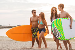 Smiling friends in sunglasses with surfs on beach Royalty Free Stock Photo