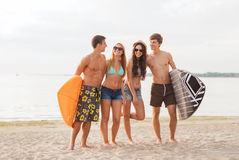 Smiling friends in sunglasses with surfs on beach. Friendship, sea, summer vacation, water sport and people concept - group of smiling friends wearing swimwear stock photography