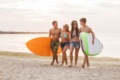 Smiling friends in sunglasses with surfs on beach Royalty Free Stock Image