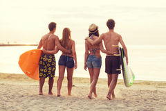 Smiling friends in sunglasses with surfs on beach. Friendship, sea, summer vacation, water sport and people concept - group of smiling friends wearing swimwear royalty free stock photography