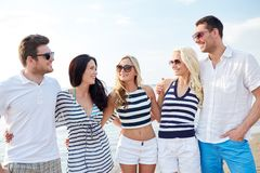 Smiling friends in sunglasses talking on beach Stock Photos