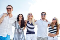 Smiling friends in sunglasses walking on beach Royalty Free Stock Photo