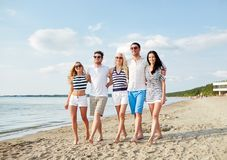 Smiling friends in sunglasses walking on beach Royalty Free Stock Photography