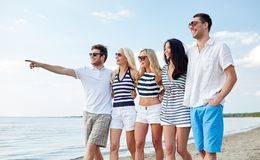Smiling friends in sunglasses walking on beach Royalty Free Stock Images