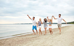 Smiling friends in sunglasses walking on beach. Summer, holidays, sea, tourism and people concept - group of smiling friends in sunglasses walking on beach stock images