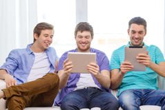 Smiling friends with tablet pc computers at home Royalty Free Stock Photography