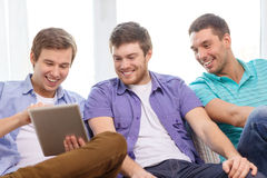 Smiling friends with tablet pc computers at home Royalty Free Stock Image