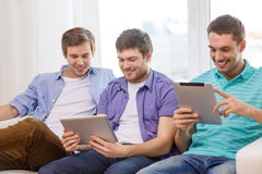 Smiling friends with tablet pc computers at home Royalty Free Stock Photos