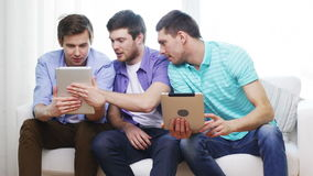 Smiling friends with tablet pc computers at home stock footage