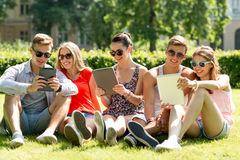 Smiling friends with tablet pc computers in park. Friendship, leisure, summer, technology and people concept - group of smiling friends with tablet pc computers Royalty Free Stock Photos